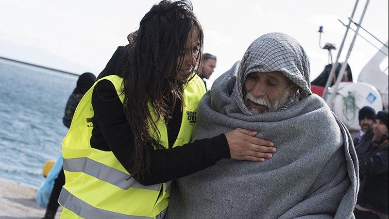 Женщина-спасатель успокаивает спасенного пожилого беженца