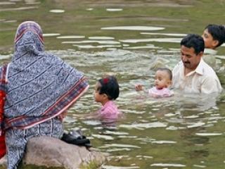 Пакистанская семья спасается от жары в городском пруду (г. Исламабад).
