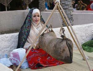 Жительница оманской этнической деревни демонстрирует одно из традиционных ремесел.