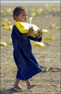 Афганский ребенок несет домой пакет с гуманитарной помощью