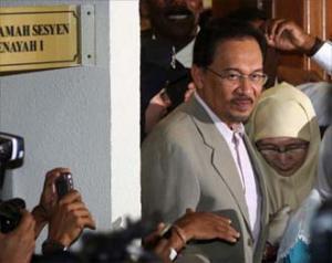 Анвар Ибрагим выходит с женой из зала суда.