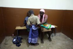 """Женщина успокаивает сына после операции обрезания в клинике """"Marie Stopes"""" в провинции Ньянза"""