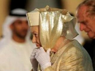 """Королева одетая в своем """"золотом"""" парчовом пальто, украшенном кристаллами Swarovski, и шляпке, поверх которой накинула золотой шарф, ставший для нее своеобразным хиджабом"""