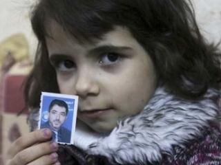 Одна из дочерей Абу-Сиси с портретом отца, похищенного Израилем год назад на территории Украины