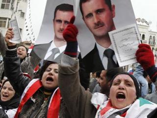 Сторонники Башара Асада держат в руках портреты президента и копии проекта новой конституции