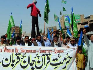 На плакате: Мы пожертвуем жизнью рад святости Корана