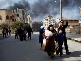 Семья убегает от ожесточенных боев между вооруженными повстанцами и правительственной армией в сирийском городе Идлиб