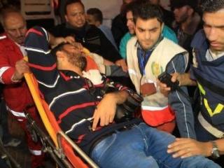 Сотрудники «Скорой помощи» выносят раненного журналиста
