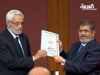 Глава конституционной ассамблеи Хисам Гарян передает проект новой конституции Мухаммеду Мурси