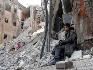Девочка сидит на руинах жилого дома в лагере Ярмук
