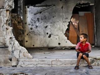 Сирийский мальчик сидит на пороге разрушенного дома