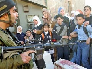 Израильский солдат нацелил автомат на палестинских женщин и детей