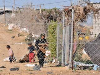 Газа. Женщина с детьми собирает дрова и бумагу для выпечки хлеба в Эзбет Абд Раббо
