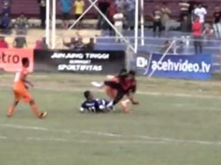 Игрок в оранжевой футболке теряет равновесие от удара