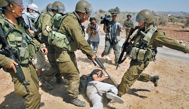 Израильские солдаты избивают ногами иностранного активиста
