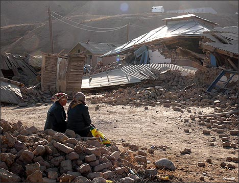 Женщины сидят возле дома, разрушенного в результате землетрясения (Фото:  Алексей Осокин)