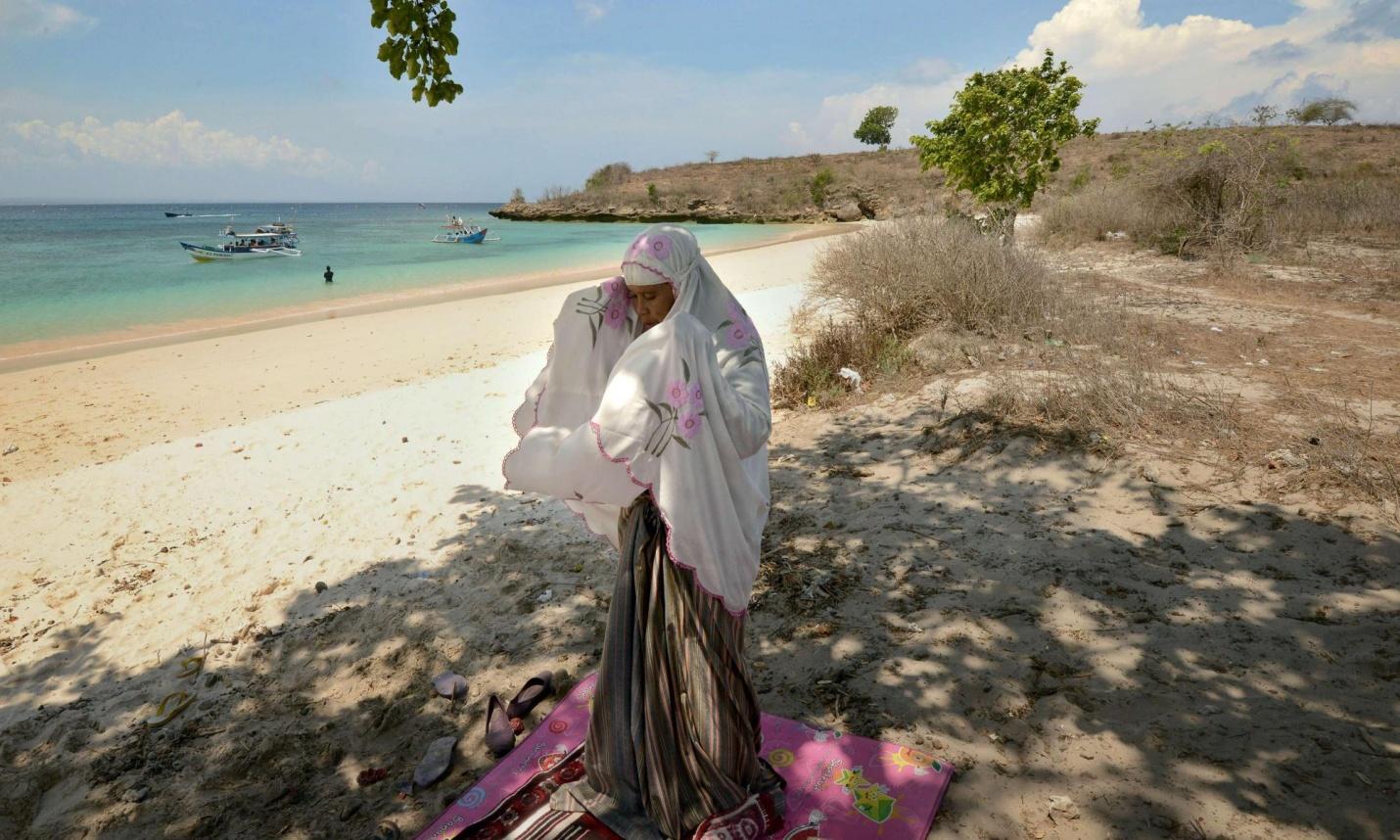 Гостья острова Ломбок совершает намаз на пляже