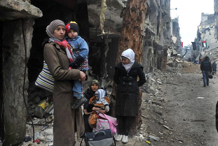 Сирийская семья на фоне разрушенного города