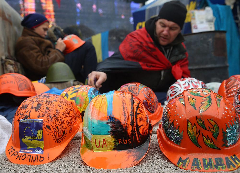 Демонстранты на киевском Майдане сидят возле разрисованных касок