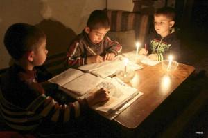 Палестинские мальчики делают уроки при свечах в отсутствии иного источника света