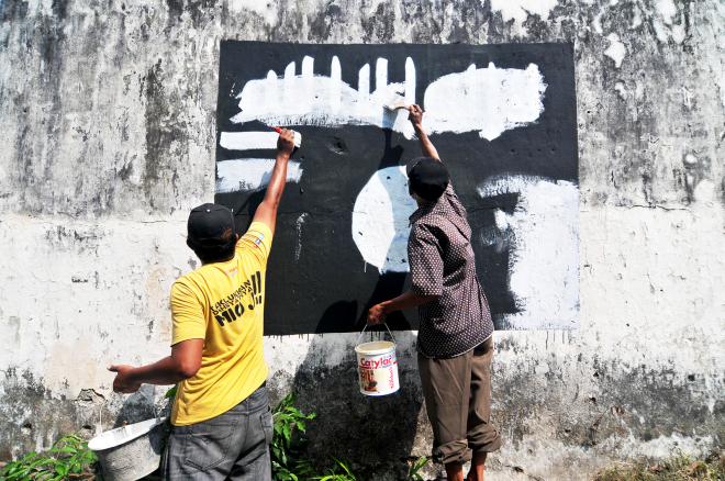 Мужчины замазывают белой краской символику ИГИЛ