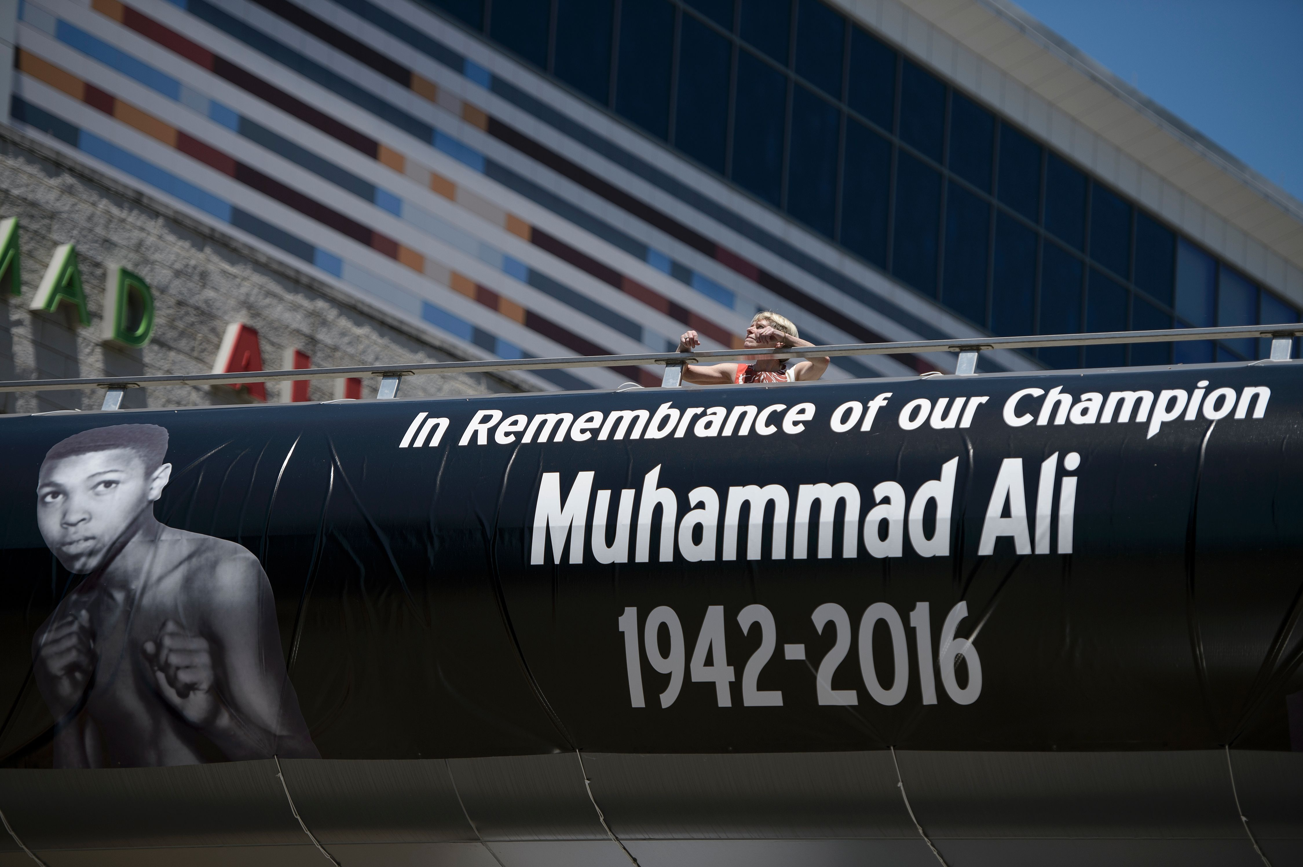 A woman walks on a pedestrian bridge from the Muhammad Ali Center June 9, 2016 in Louisville, Kentucky. Two days of funeral ceremonies bidding farewell to Muhammad Ali got underway Thursday with a Muslim prayer service in the Kentucky hometown of the beloved boxing legend and civil rights hero. / AFP / Brendan Smialowski