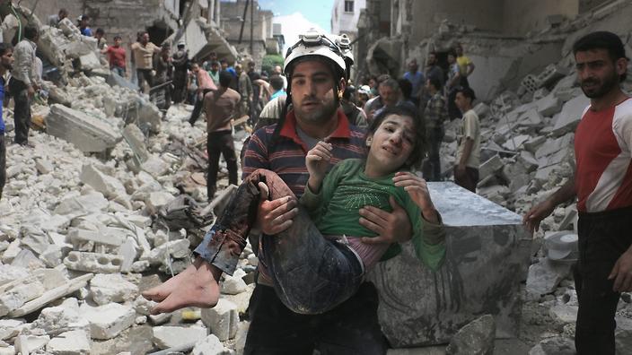 Спасатель несет на руках ребенка, раненного в результате бомбардировки в Алеппо