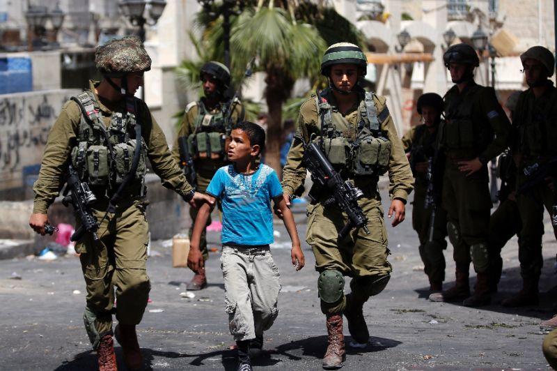 Израильские военные ведут задержанного палестинского мальчика