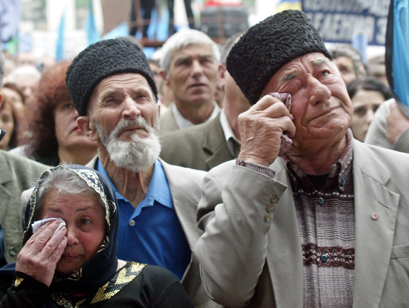 Crimean Tatars wipe their tears at a mourning rally during the 60th anniversary of deportation of ethnic Tatars under Soviet dictator Josef Stalin, in the Crimean capital of Simferopol, Ukraine, Tuesday, May 18, 2004. Thousands of people gathered in Simferopol main square to honor the memory of victims of the Soviet regime (AP Photo/Efrem Lukatsky)