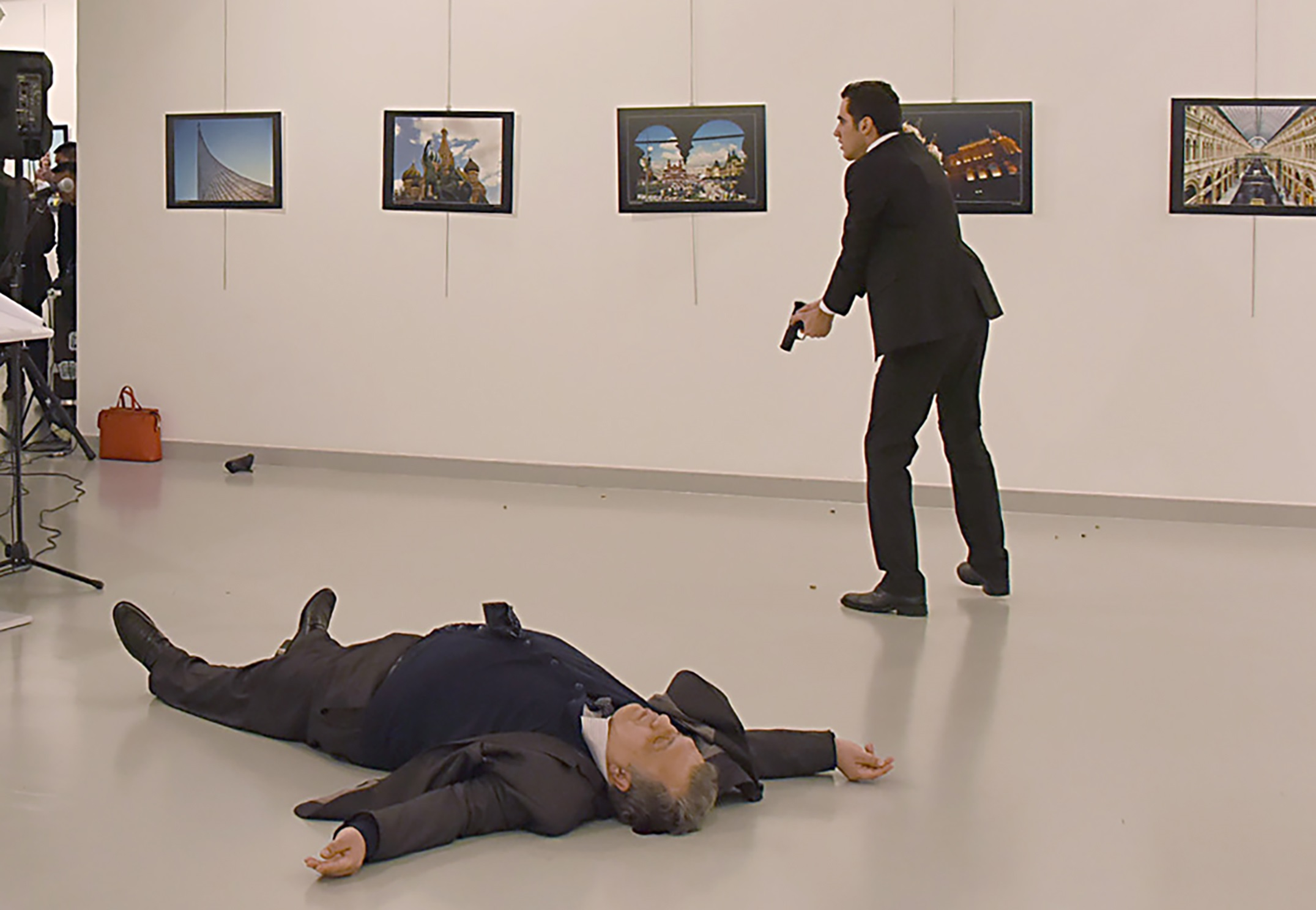 This picture taken on December 19, 2016 shows Andrey Karlov (L), the Russian ambassador to Ankara, lying on the floor after being shot by a gunman (R) during an attack during a public event in Ankara. A gunman crying «Aleppo» and «revenge» shot Karlov while he was visiting an art exhibition in Ankara on December 19, witnesses and media reports said. The Turkish state-run Anadolu news agency said the gunman had been «neutralised» in a police operation, without giving further details. / AFP PHOTO / Sozcu daily / Yavuz Alatan / Turkey OUT