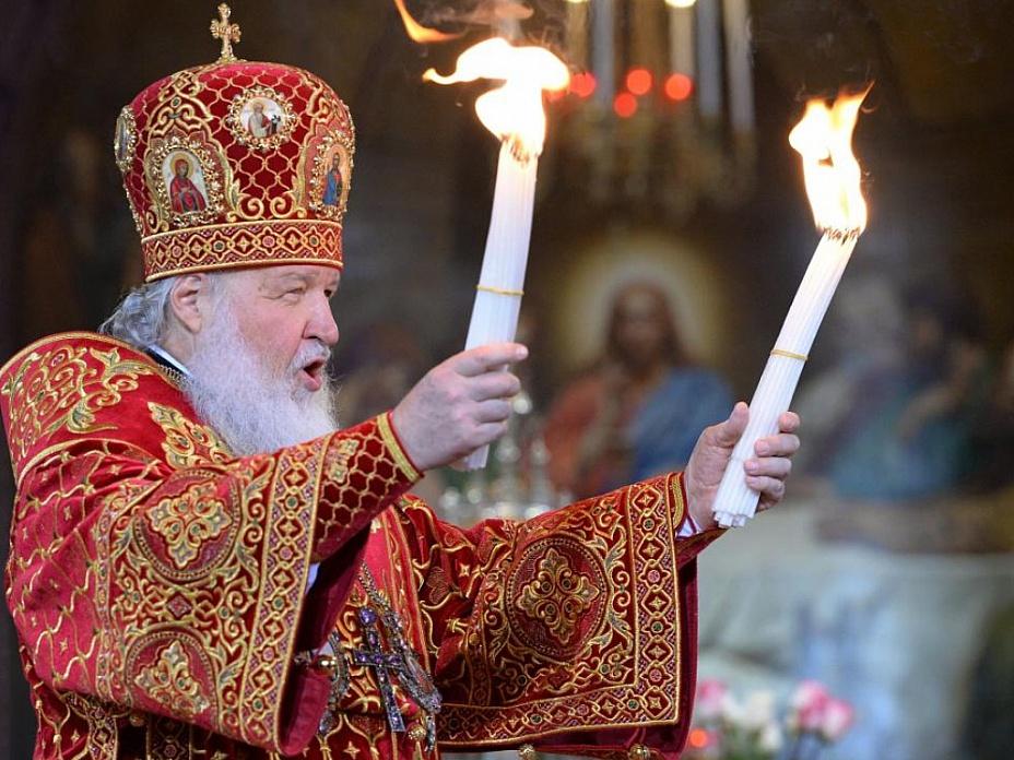 Патриарх Кирилл демонстрирует верующим благодатный огонь