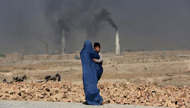 Женщина с ребенком на руках идет мимо кирпичного завода на окраине Кабула (Фото: РИА Новости)