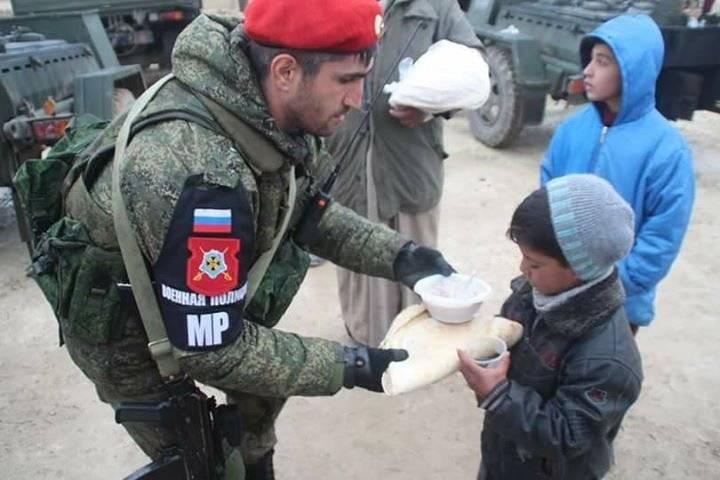Российский военный полицейский дает еду мальчику в Сирии