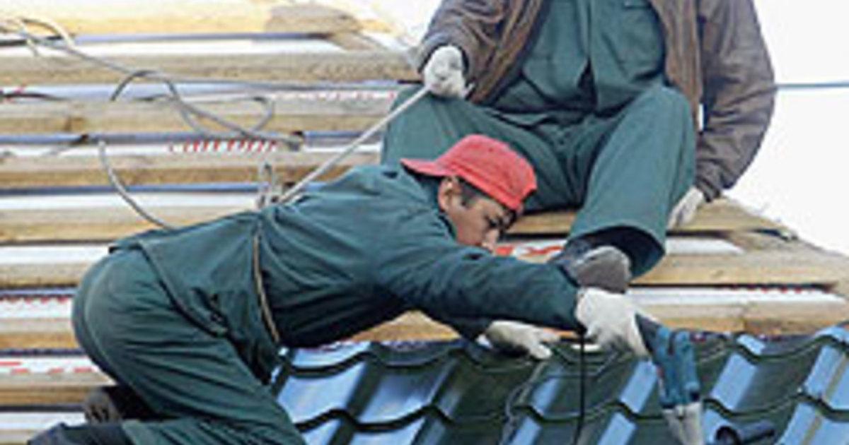 Рабочие-мигранты на строительстве котеджа