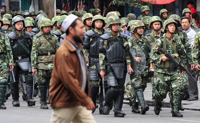Мусульманин-уйгур проходит мимо силовиков