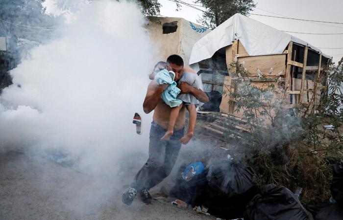Мужчина спасает ребенка при пожаре в лагере для беженцев «Мориа». Фото: Reuters