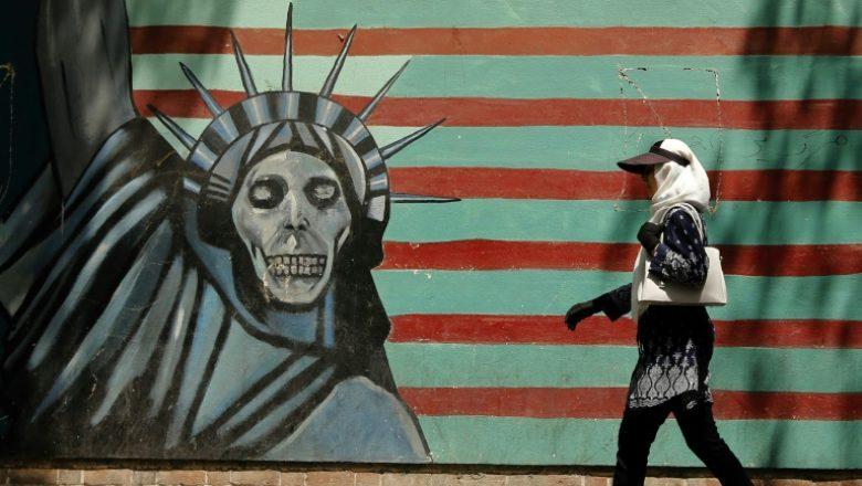 Жительница Ирана на фоне антиамериканского граффити