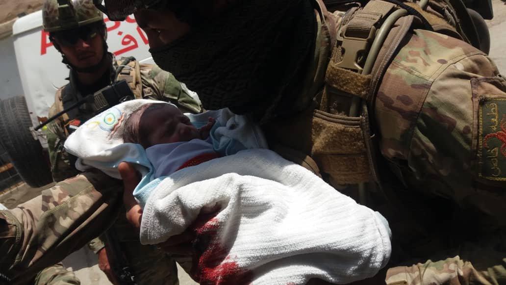 Военнослужащий несет в руках маленькую жертву теракта