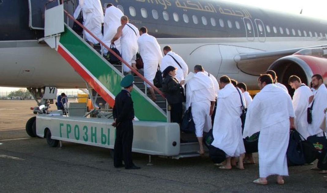 Российские мусульмане поднимаются на борт самолета, чтобы отправиться в хадж