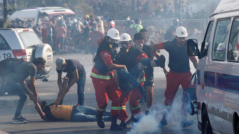 Сотрудники скорой помощи несут пострадавшего демонстранта