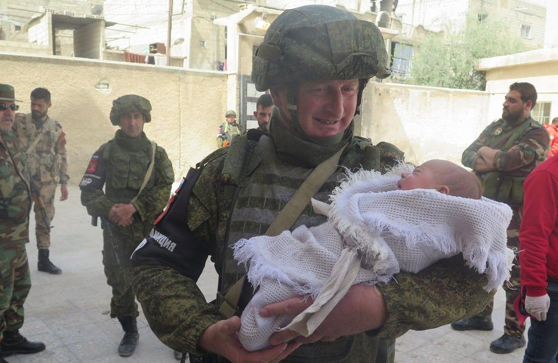 Сотрудник военной полиции РФ с младенцем на руках в Сирии