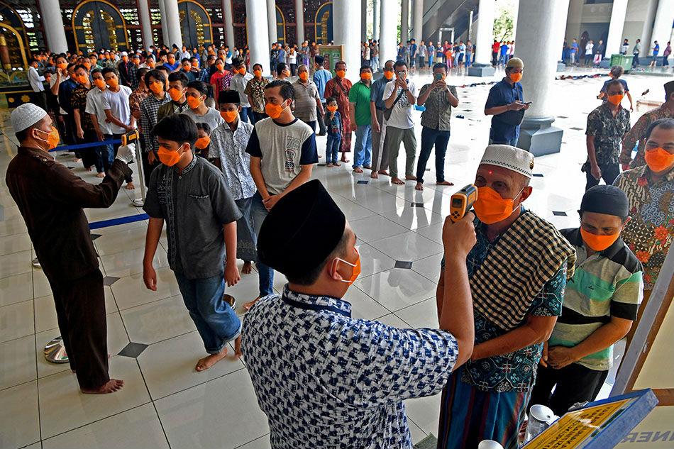 Верующие у входа в одну из мечетей в Индонезии
